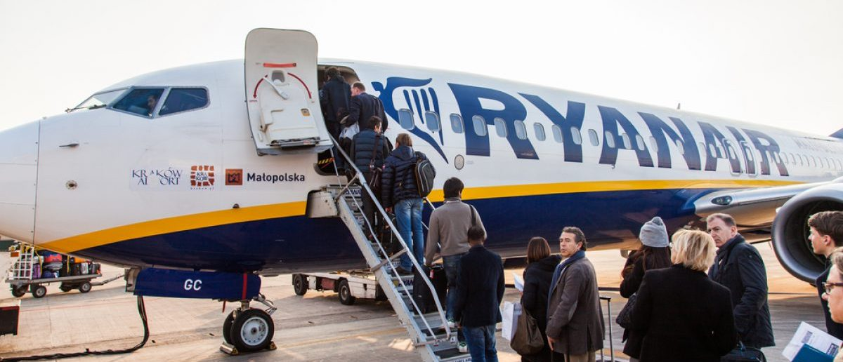Passengers boarding an airplane set to embark. [Caracarafoto / Shutterstock.com]