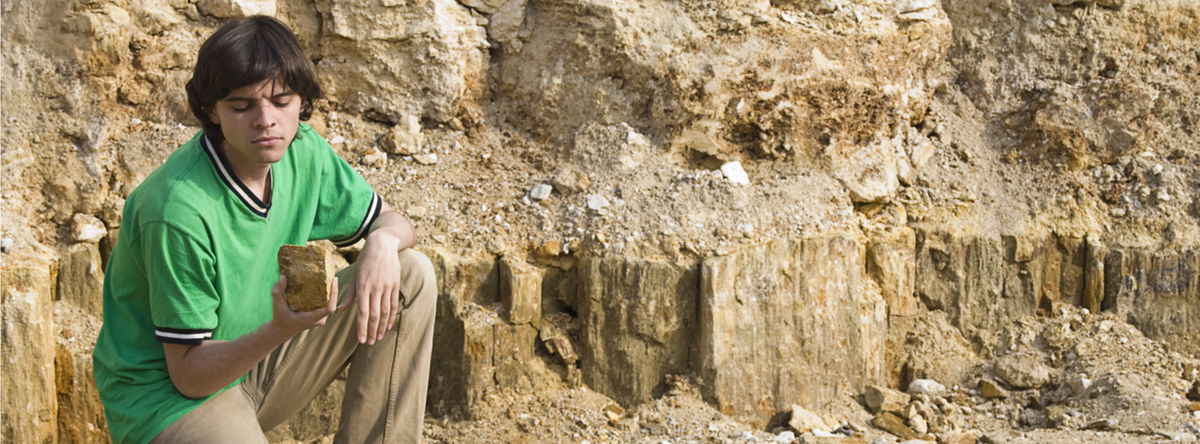 A geology student intently studies a rock. (Photo: Shutterstock/Yarchyk)