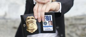 FBI agent holds a badge (Shutterstock/Peter Kim)