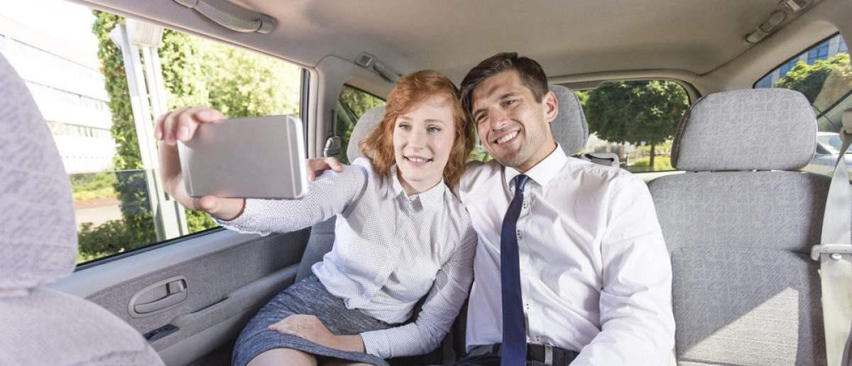 Two people enjoying a ride together in the backseat. [Shutterstock - Photographee.eu]