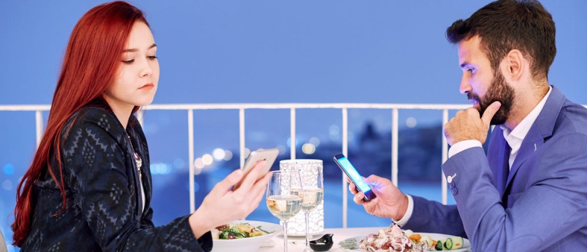A young couple at dinner using their mobile phones. [Shutterstock - astarot]
