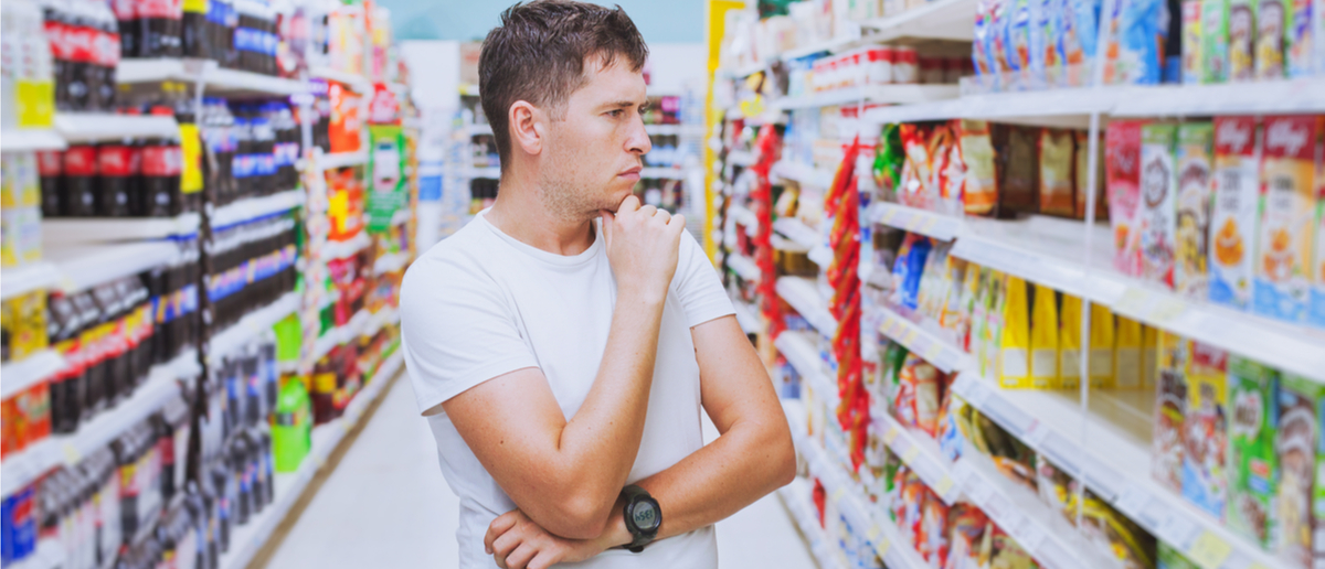 Man ponders his food choices at a grocery store (Photo: Shutterstock/Ditty_about_summer)