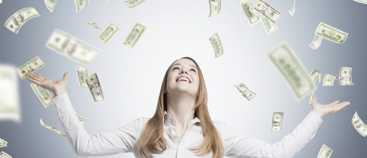 Dollars from falling the sky and into the palms of a female tech worker. [Shutterstock - ImageFlow]