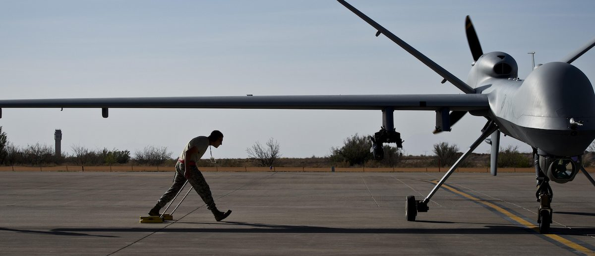 After taxiing in an MQ-9 Reaper, Airman 1st Class Jon Mann walks under a Reaper's wing to place wheel chocks to prevent accidental movement April 24, 2013 at Holloman Air Force Base, N.M. The crew chiefs are responsible for taxiing incoming aircrafts and performing post-flight checks that include fluid checks, looking over the aircraft for damage and cleaning the aircraft. (U.S. Air Force photo/Senior Airman Andrew Lee)