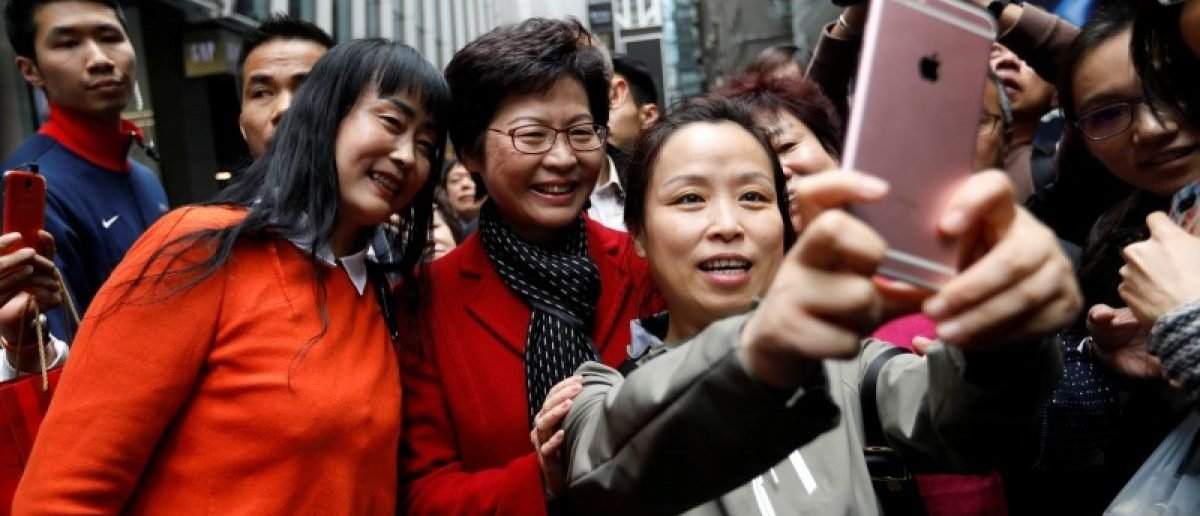 People take selfies with Carrie Lam, chief executive-elect, a day after she was elected in Hong Kong, China March 27, 2017.REUTERS/Tyrone Siu