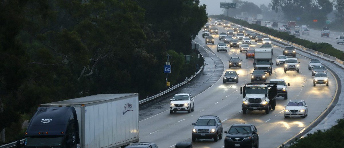 Traffic moves through the rain along interstate 5 in Encinitas, California December 3, 2014. Nearly two-thirds of Americans would support roadway user fees to help fix the country's crumbling transportation infrastructure, according to a survey to be published on April 28, 2016 that was seen by Reuters. REUTERS/Mike Blake