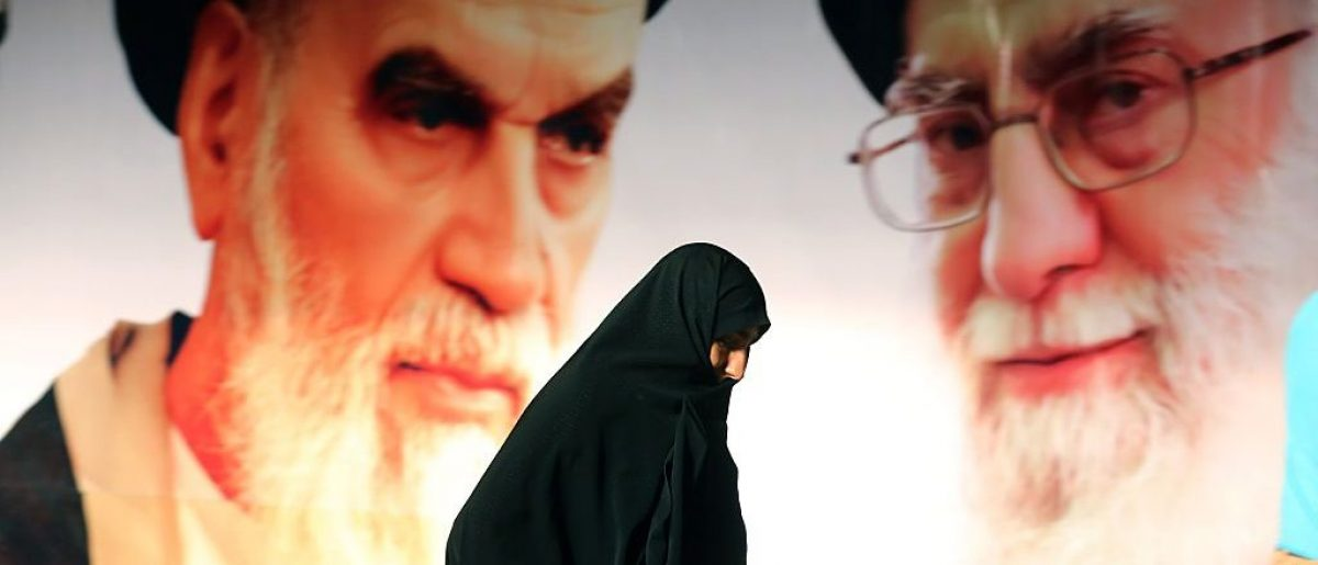 An Iranian woman walks past a giant poster showing supreme leader, Ayatollah Ali Khamenei (R) and the founder of Iran's Islamic Republic, Ayatollah Ruhollah Khomeini (L) during a ceremony marking the 36th anniversary of his return from exile on February 1, 2015 at Khomeini's mausoleum in a suburb of Tehran. (Photo credit: ATTA KENARE/AFP/Getty Images)
