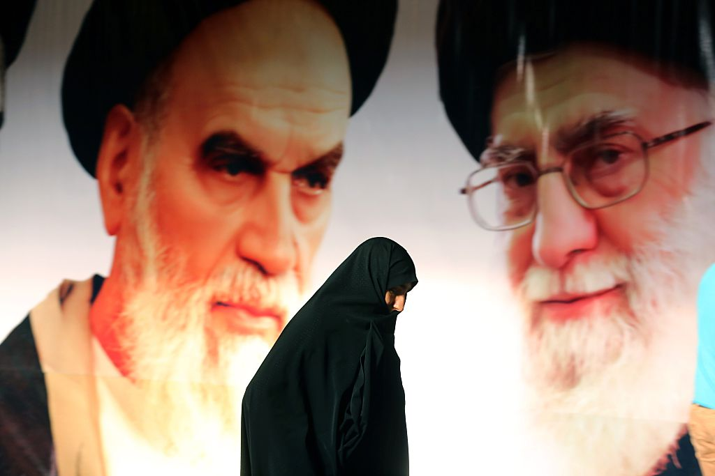 An Iranian woman walks past a giant poster showing supreme leader, Ayatollah Ali Khamenei and the founder of Iran's Islamic Republic, Ayatollah Ruhollah Khomeini (Getty Images)