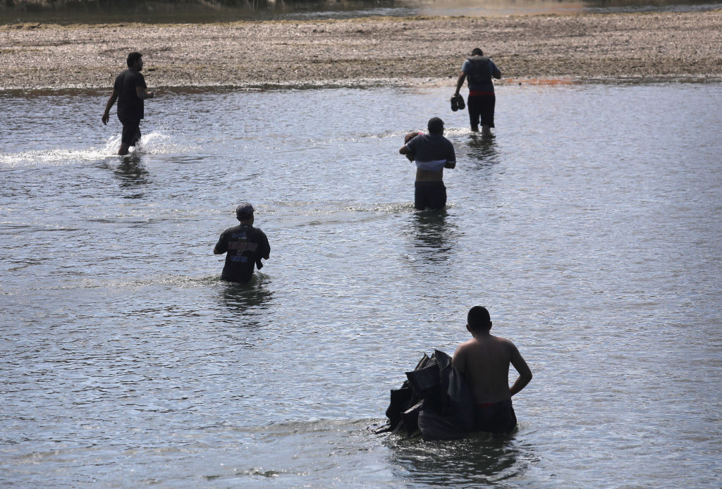"ROMA, TX - MARCH 14: A smuggler, also known as a ""coyote,"" carries life jackets while walking a group of undocumented immigrants across the shallow Rio Grande at the U.S.-Mexico border on March 14, 2017 in Roma, Texas. U.S. Border Patrol agents intercepted them on the Texas side of the river and pushed them back into Mexico. (Photo by John Moore/Getty Images)"