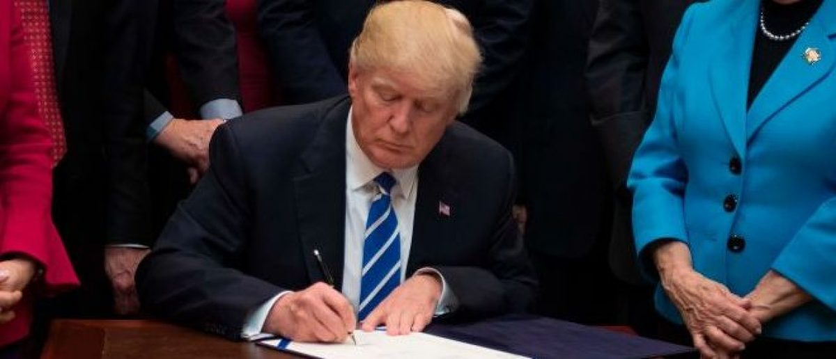 US President Donald Trump (C) signs H.J. Resolution 37 after signing it at the White House in Washington, DC, March 27, 2017. / AFP PHOTO / JIM WATSON        (Photo credit should read JIM WATSON/AFP/Getty Images)