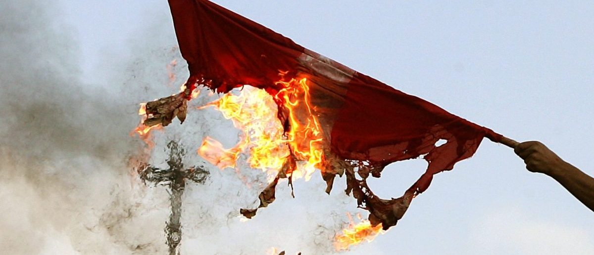 A Palestinian holds a burning Danish flag in front of the Church of Nativity in the West Bank city of Bethlehem February 6, 2006. REUTERS/Damir Sagolj