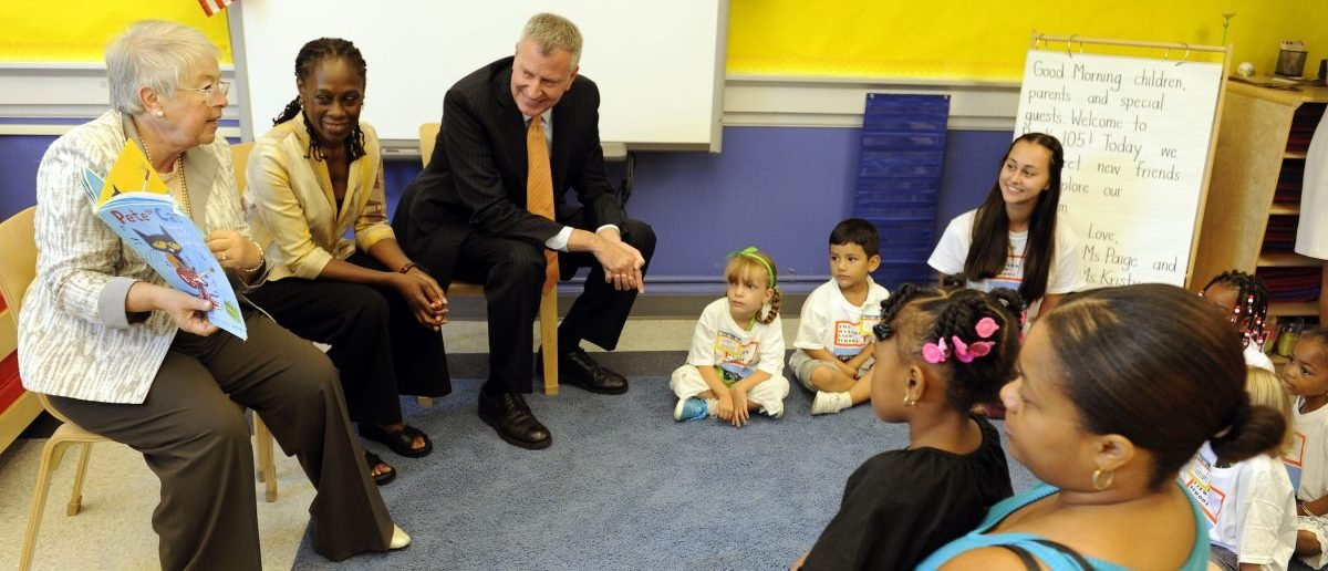 New York City Chancellor Carmen Farina (L) reads a book to first time teacher Paige Buono's class as first lady Chirlane McCray (2nd L) and Mayor Bill de Blasio look on during the first day of school at Public School 59 in Staten Island, New York, September 9, 2015.   REUTERS/Barry Williams/Pool - RTSBT0