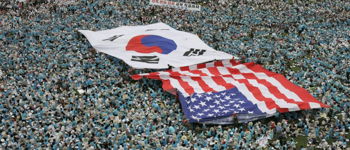 Christians and conservative rightists carry a South Korea flag and a U.S. flag above their heads during an anti-North Korea and pro-U.S. rally marking Memorial Day in Seoul June 6, 2007. Police said about 20,000 people, mostly Christians, attended the rally on Wednesday. REUTERS/Lee Jae-Won