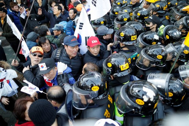 Supporters of impeached President Park Geun-hye scuffle with riot police during a protest after Park's impeachment was accepted, near the Constitutional Court in Seoul, South Korea, March 10, 2017. REUTERS/Kim Hong-Ji