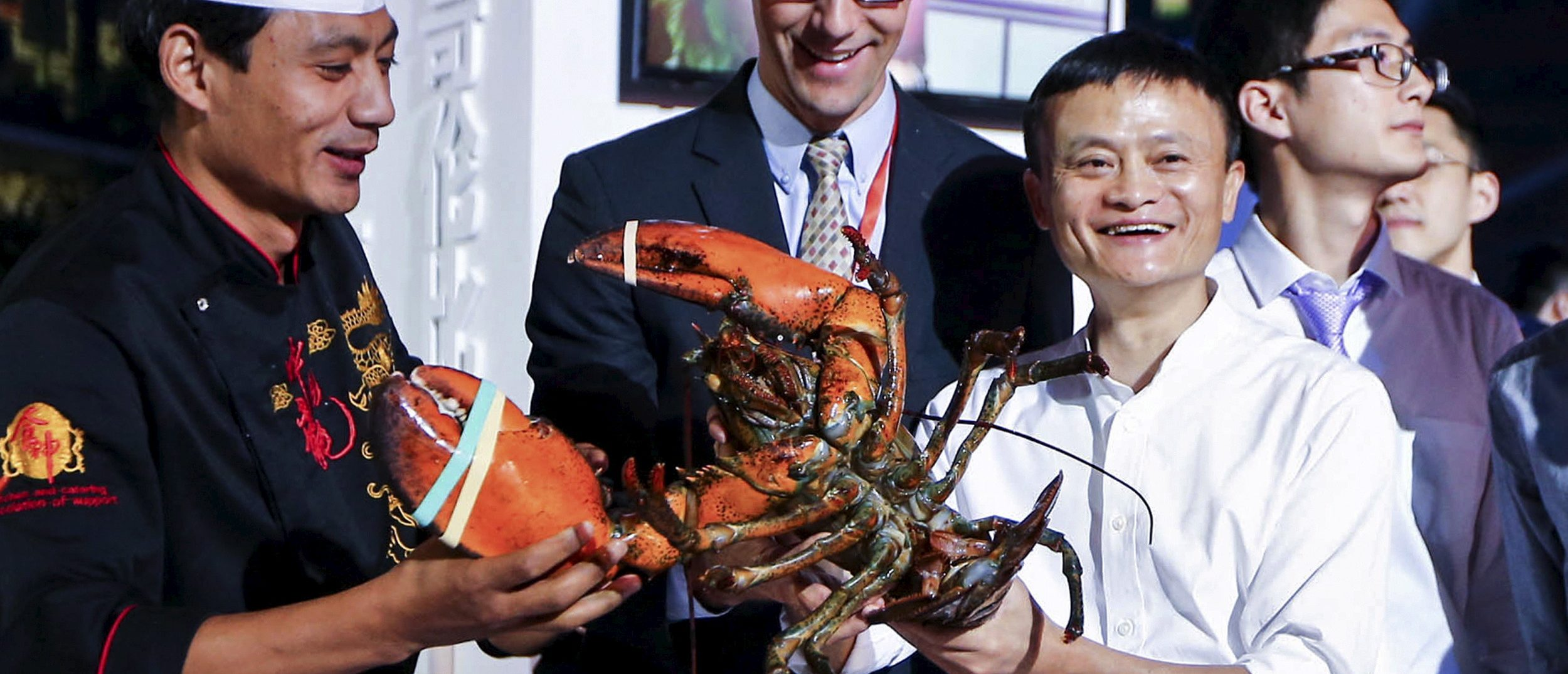 Alibaba Group's executive chairman Jack Ma (R, in white) holds a lobster (PHOTO: REUTERS/Stringer)
