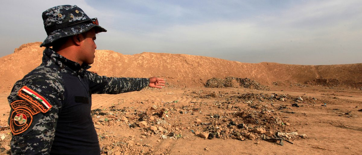A member of Iraqi security forces gestures towards a mass grave for corpses in the town of Hammam al-Alil which was seized from Islamic State last week, Iraq November 9, 2016. REUTERS/Alaa Al-Marjani -
