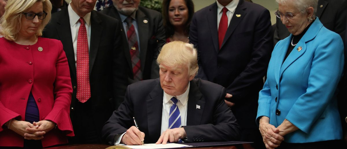 U.S. President Donald Trump signs H.J. Res. 37, in the Roosevelt room of the White House in Washington, U.S., March 27, 2017. (Photo: REUTERS/Carlos Barria)