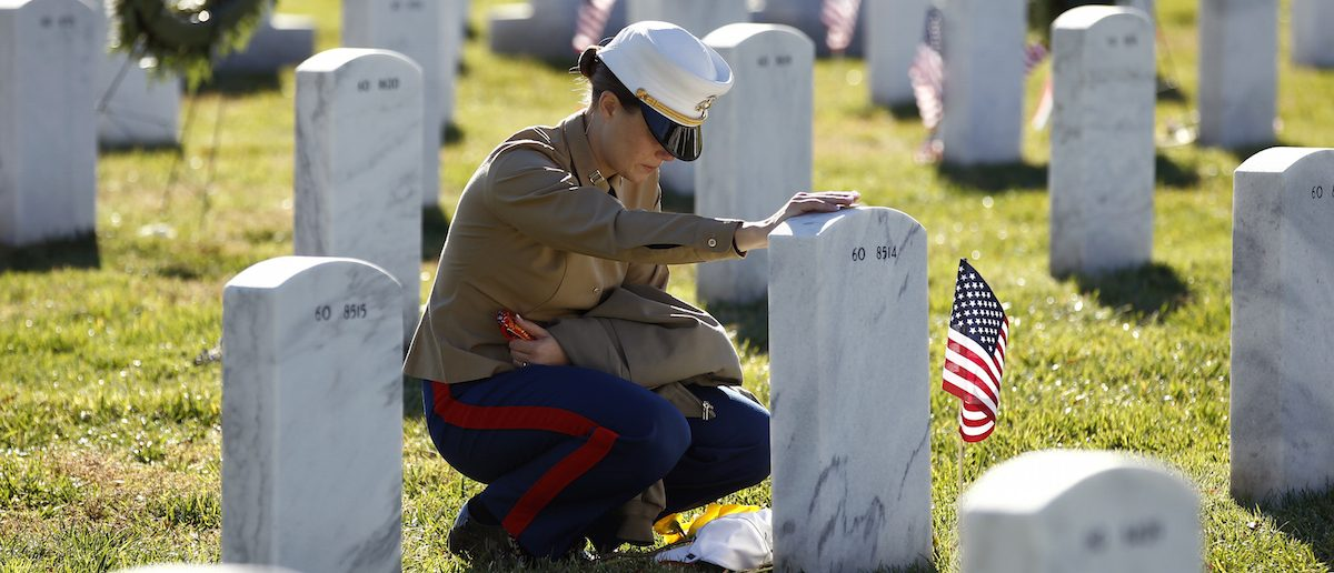 U.S. Marine Capt. Jill A. Leyden touches the grave of her friend Major Megan M. McClung at Arlington National Cemetery.