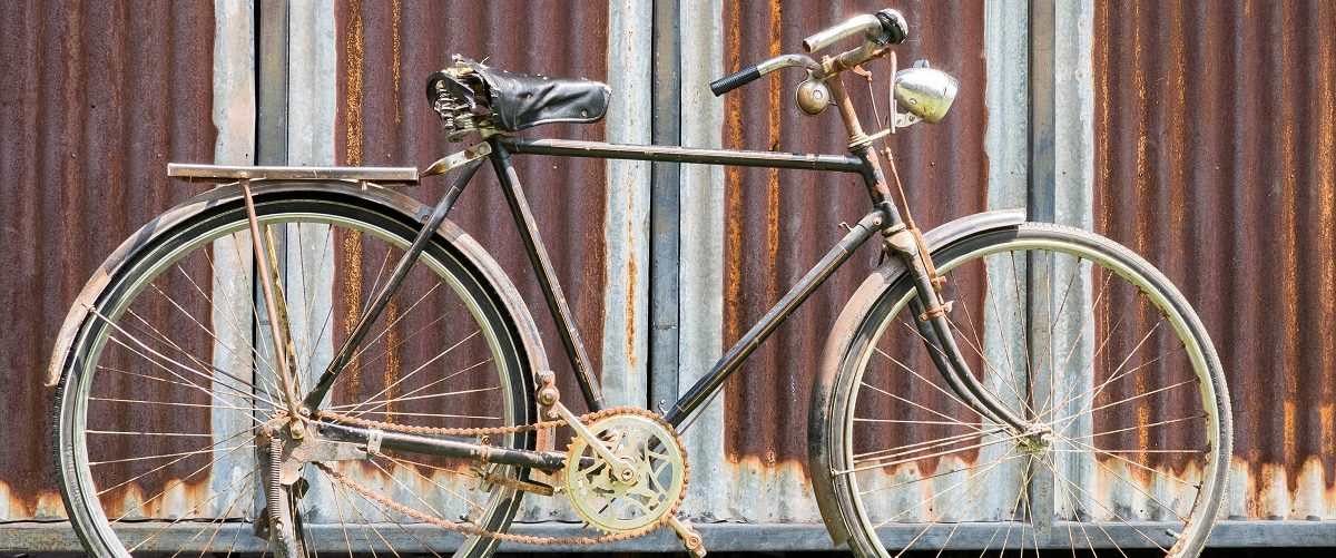 Old bicycle displayed against a metal sheet background. niceregionpics/Shutterstock.