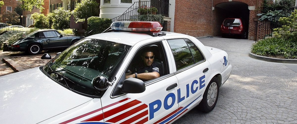 District of Columbia Metro Police stand guard in the driveway where Alan Senitt, 27, was stabbed and his throat was slashed on July 10, 2006 in a Georgetown neighborhood in Washington, DC. Chip Somodevilla/Getty Images.