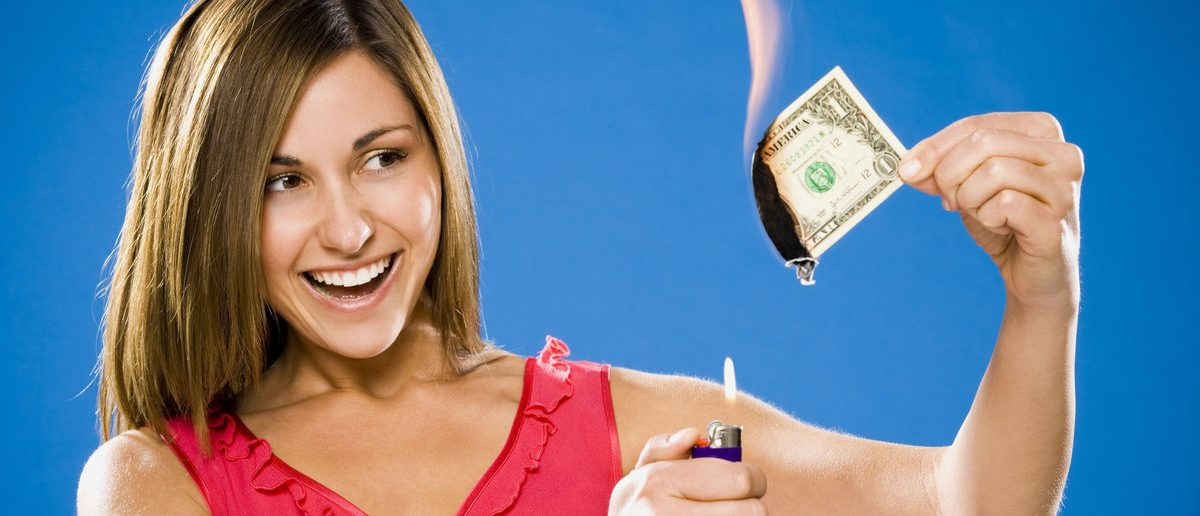 Woman setting American one dollar bill on fire (Shutterstock/Alan Bailey)