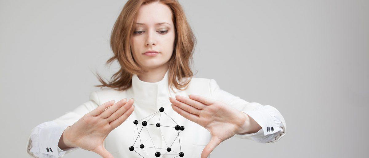 Woman scientist holding model of molecule or crystal lattice. (Shutterstock/Merkushev Vasiliy)