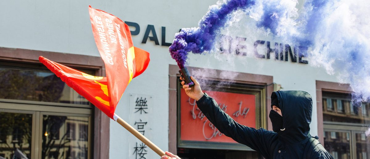 STRASBOURG, FRANCE - APR 20, 2016:Man holding smoke grenade as hundreds of people demonstrate as part of nationwide day of protest against proposed labor reforms by Socialist Government (Shutterstock/408992974)