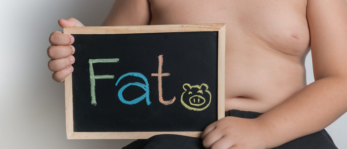 obese fat boy holding blackboard on gray background (Shutterstock/kwanchai.c)