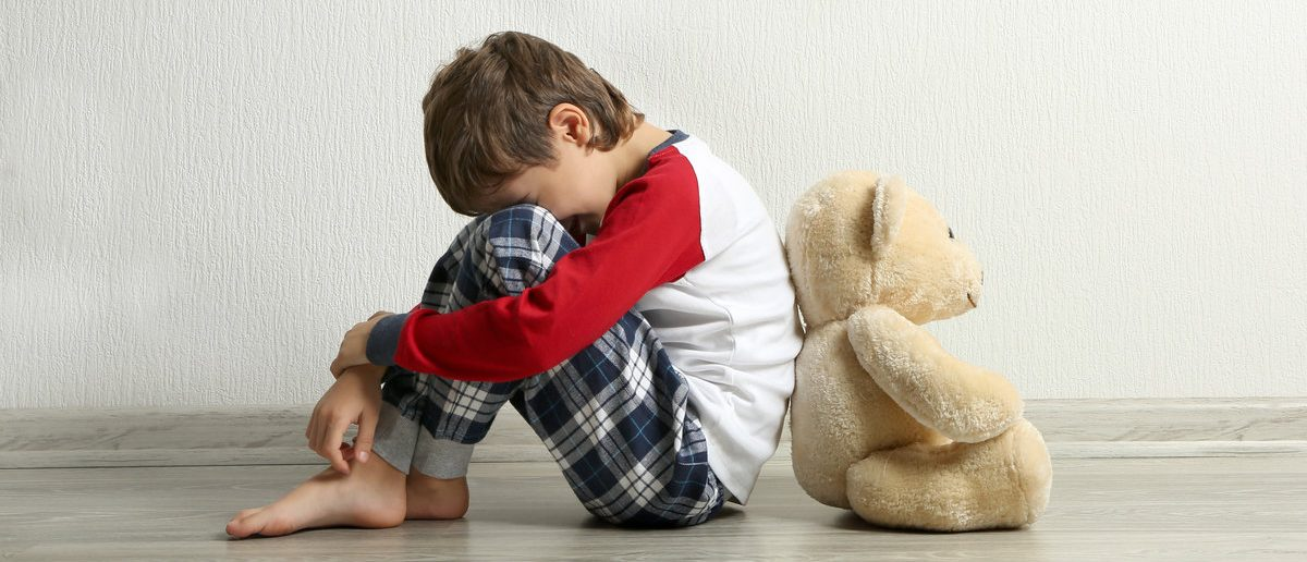 Sad little boy with teddy bear sitting on floor in empty room (Shutterstock/Africa Studio )