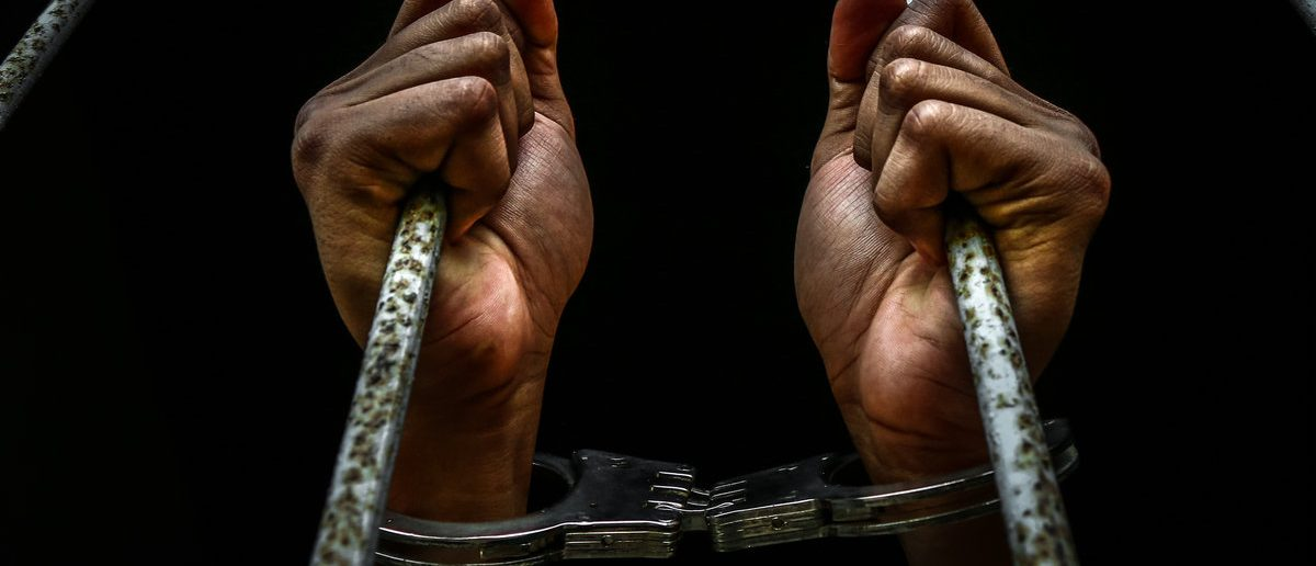 Human hand of prisoner on steel lattice close up. (Shutterstock/Thawornnurak)
