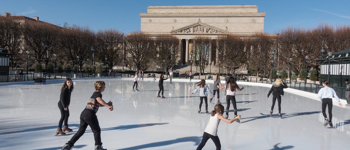WASHINGTON DC - FEB 23, 2017: Ice skaters dressed for spring skate under 74 degree (F) sun in unseasonably warm winter weather at National Gallery of Art Sculpture Garden Ice Rink on the National Mall (Shutterstock/bakdc)