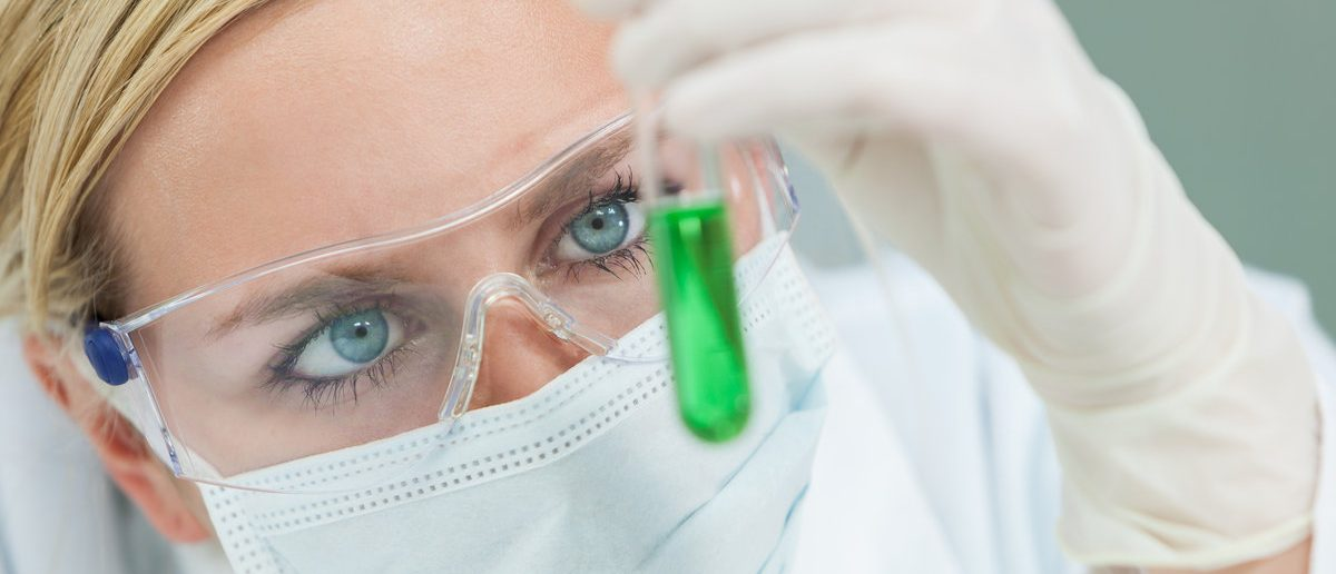 Female medical or research scientist or doctor using looking at a test tube of green solution in a lab or laboratory (Shutterstock/Darren Baker)