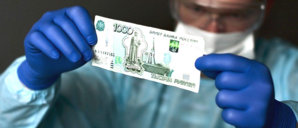 Man with rubber gloves holding bill denoting 1000 Russian rubles. [Shutterstock - Paravyan Eduard]