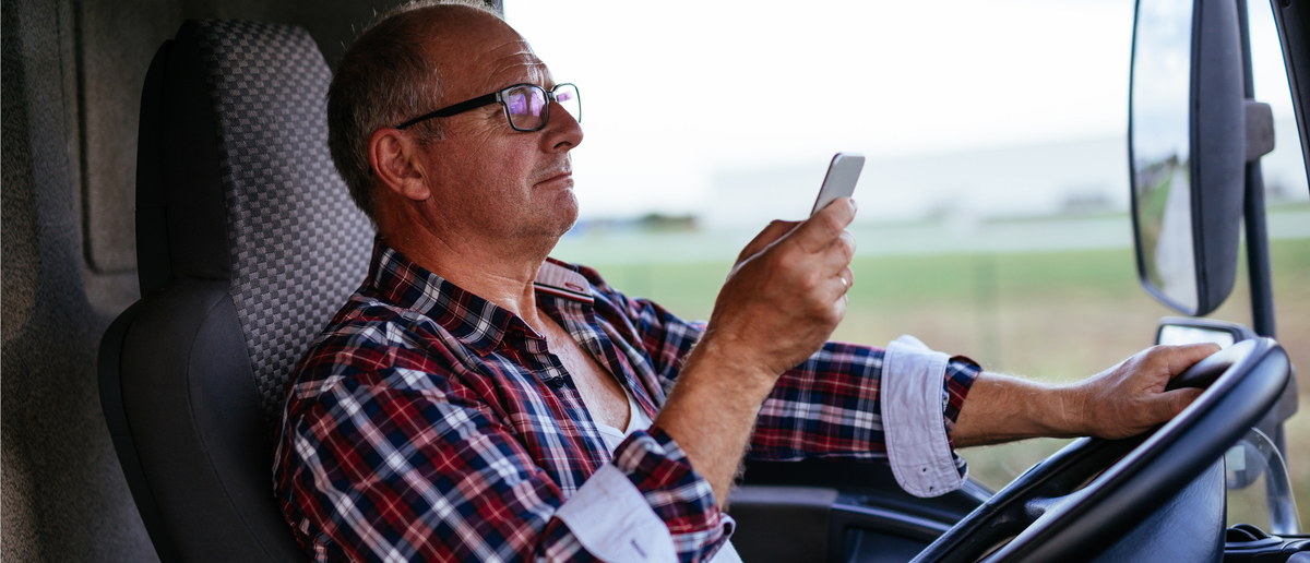 A truck driver reads on his phone while driving (Photo: Shutterstock/bbernard)