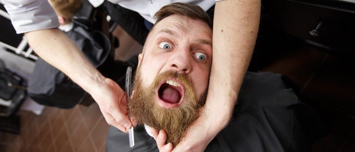 A man has his beard shaved. (Shutterstock/David Tadevosian)