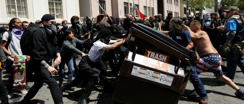 Demonstrators for (R) and against (L) U.S. President Donald Trump push a garbage container toward each other during a rally in Berkeley, California in Berkeley, California, U.S., April 15, 2017. REUTERS/Stephen Lam