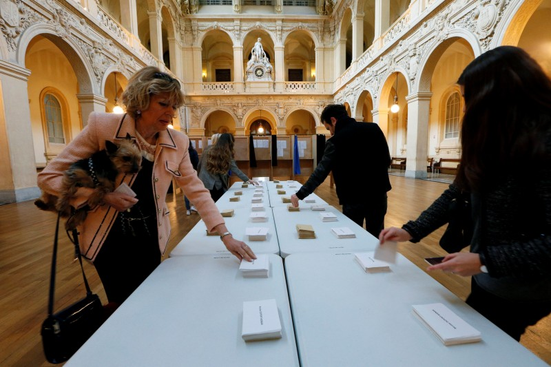 People choose their ballots before voting in the first round of 2017 French presidential election at a polling station in Lyon, France, April 23, 2017. REUTERS/Robert Pratta