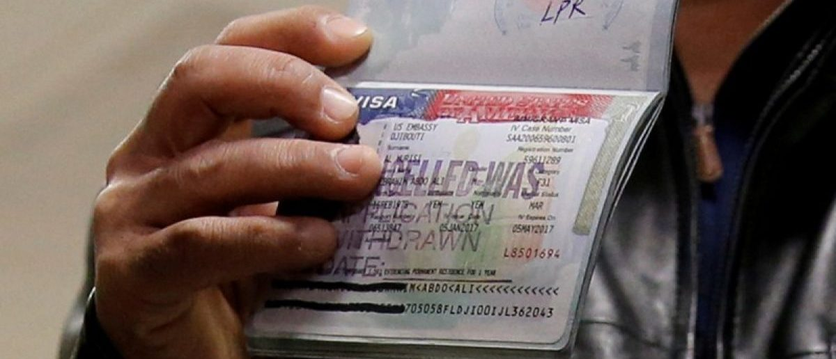 A member of the Al Murisi family, Yemeni nationals who were denied entry into the U.S. last week because of the recent travel ban, shows the cancelled visa in their passport from their failed entry to reporters as they successfully arrive to be reunited with their family at Washington Dulles International Airport in Chantilly, Virginia, U.S. February 6, 2017. REUTERS/Jonathan Ernst