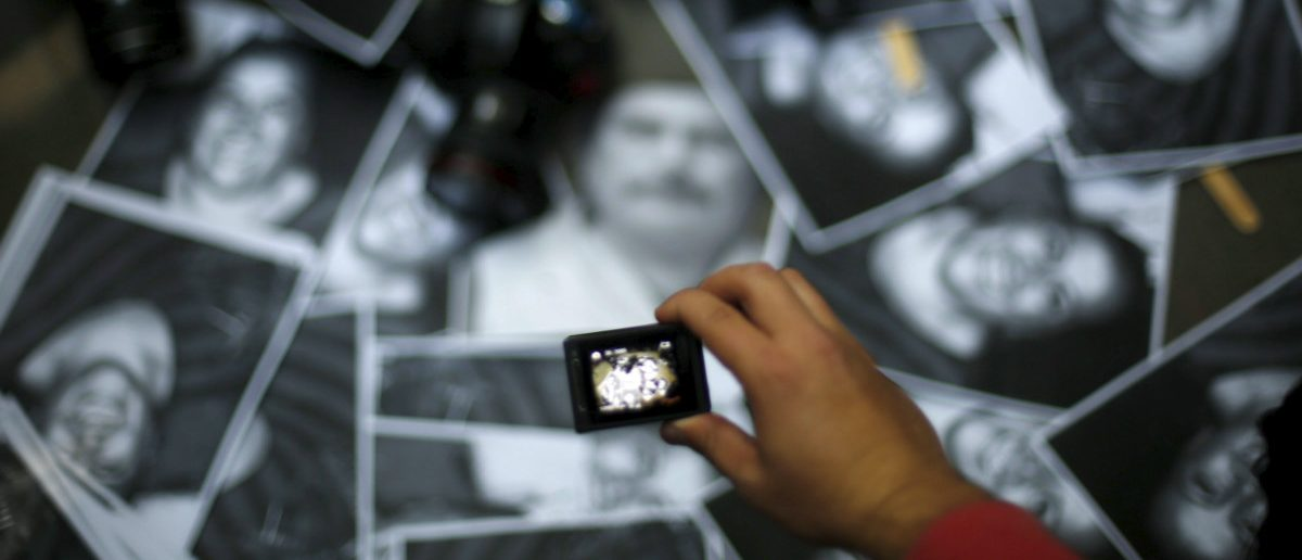 A woman takes photos of images of murdered journalists during a demonstration against the murder of a journalist (REUTERS/Edgard Garrido)