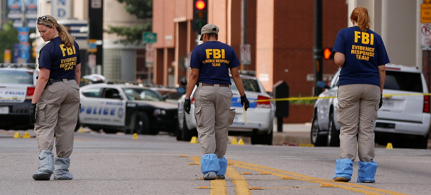 Members of the FBI Evidence Response Team survey the crime scene two days after a lone gunman ambushed and killed five police officers at a protest decrying police shootings of black men, in Dallas, Texas, U.S., July 9, 2016. (PHOTO: REUTERS/Shannon Stapleton)