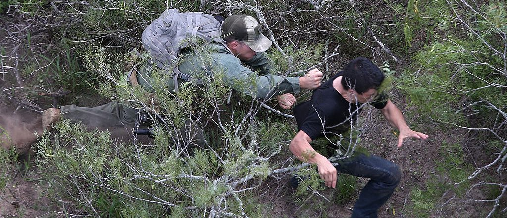 ALFURRIAS, TX - SEPTEMBER 09: A U.S. Border Patrol agent tries to tackle an undocumented immigrant in dense underbrush on September 9, 2014 near Falfurrias, Texas. He missed but the immigrant was later caught by a fellow agent. Thousands of migrants continue to cross illegally from Mexico into the United States, and Texas' Rio Grande Valley has more traffic than any other sector of the U.S.-Mexico border. (Photo by John Moore/Getty Images)