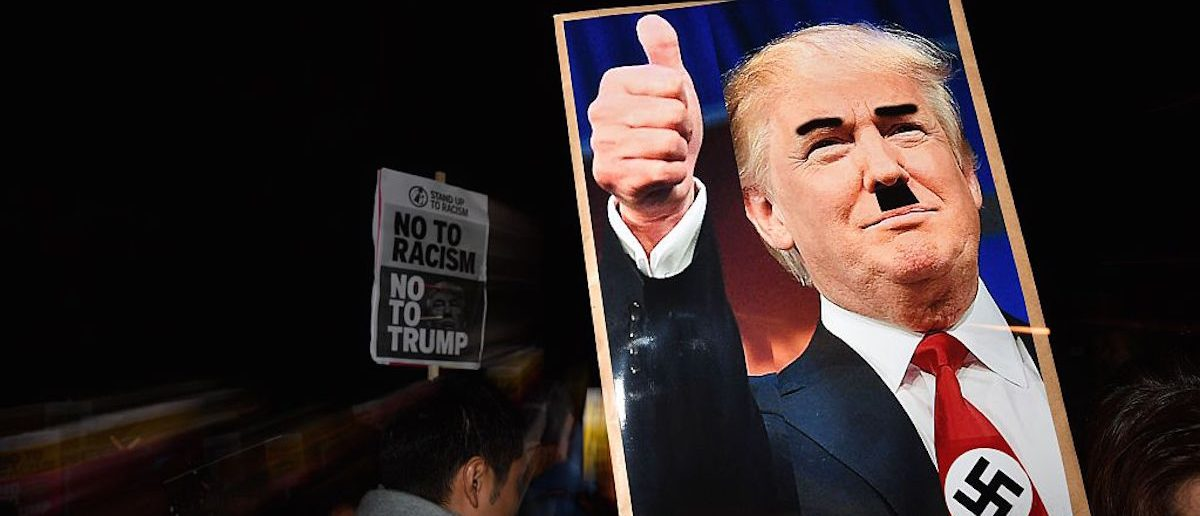 A demonstrator holds a placard showing a picture of US President-elect Donald Trump modified to add a swastika and an Adolf Hitler-style moustache during a protest outside the US Embassy in London November 9, 2016 (Photo: BEN STANSALL/AFP/Getty Images)