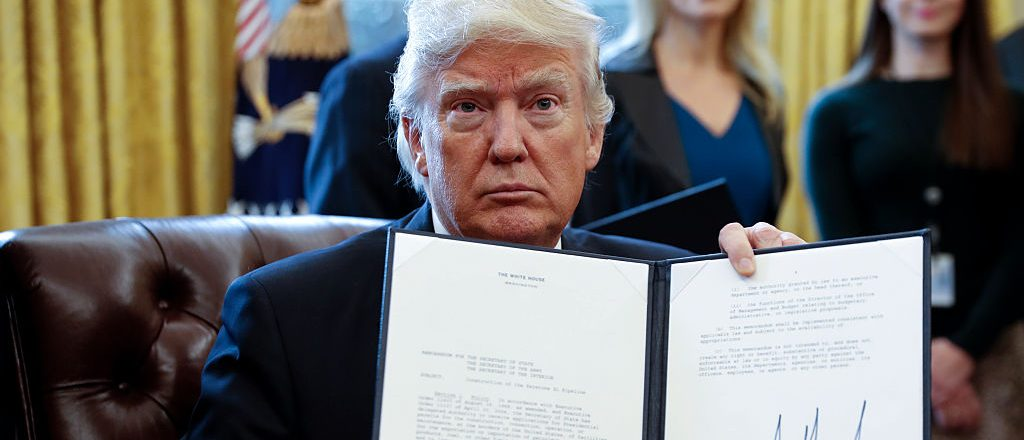 President Donald Trump displays one of five executive orders he signed related to the oil pipeline industry in the oval office of the White House January 24, 2017 in Washington, D.C. (Photo by Shawn Thew-Pool/Getty Images)q