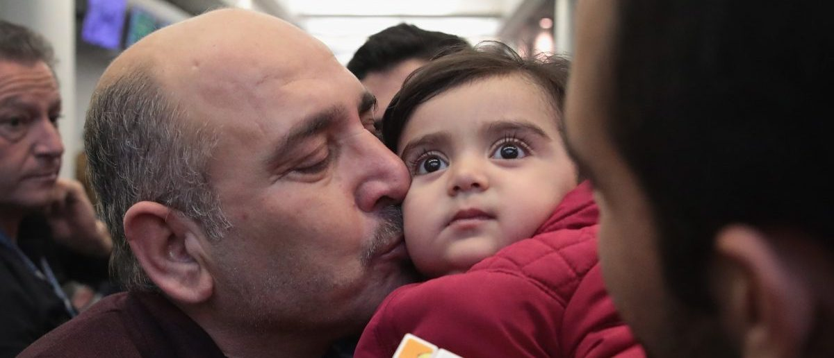 Khaled Haj Khalaf kisses his grandaughter Shams after she arrived with her mother and father at O'Hare Airport on a flight from Istanbul, Turkey on February 7, 2017 in Chicago, Illinois. (Scott Olson/Getty Images)