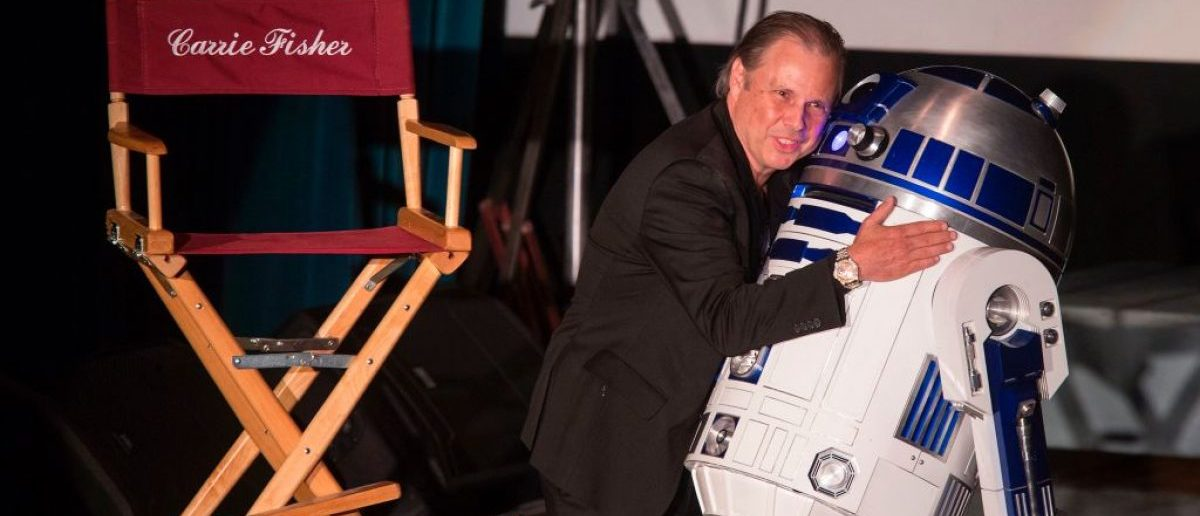 Todd Fisher hugs an R2-D2 robot near an empty chair for his late sister, actress Carrie Fisher. [Photo: DAVID MCNEW/AFP/Getty Images]