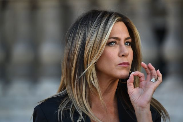 Jennifer Aniston gestures as she poses during a photocall ahead of a diner for the launch of a Louis Vuitton leather goods collection in collaboration with US artist Jeff Koons, at the Louvre in Paris on April 11, 2017. (Photo credit: GABRIEL BOUYS/AFP/Getty Images)