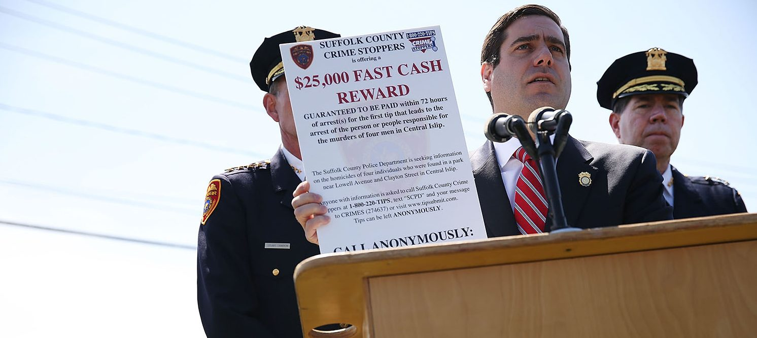 "CENTRAL ISLIP, NY - APRIL 13: Suffolk County Police Commissioner Timothy Sini holds up a notice at a news conference offering aÊ$25,000 ""fast cash reward"" for any information that leads to an arrest in the killings of four young men on April 13, 2017 in Central Islip, New York. Four mutilated bodies of young men were found in a public park and are consistent with murders of the notorious MS-13 street gang which has terrorized Central Islip and a number of other Long Island towns with large Latino populations. (PHOTO: Spencer Platt/Getty Images)"