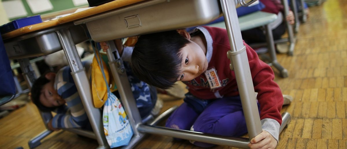 School children take shelter under desks during an earthquake simulation exercise at an elementary school in Tokyo March 11, 2015. The school in one of the central wards in Tokyo held an annual evacuation drill to prepare for earthquakes, on the fourth anniversary of the March 11, 2011 earthquake and tsunami that killed thousands and set off a nuclear crisis. REUTERS/Issei Kato