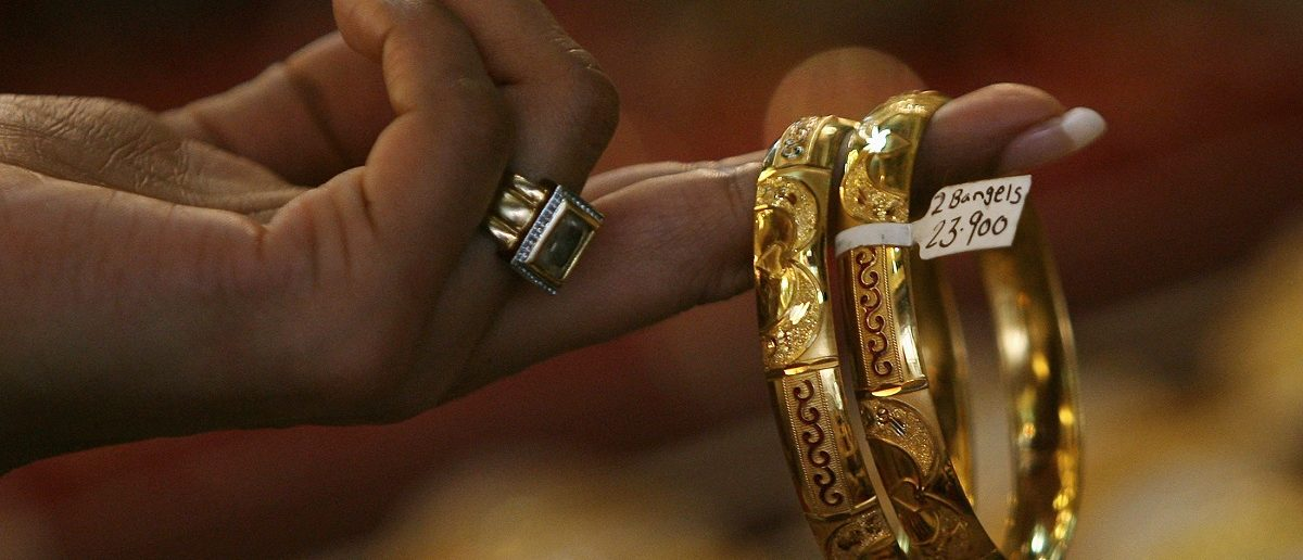 A female customer looks at gold bangles at a jewellery shop. REUTERS/Arko Datta