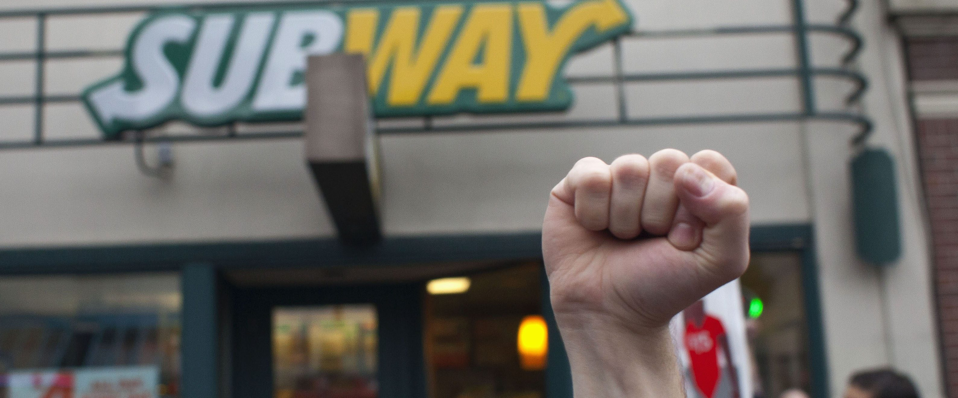 Stephen Baldwin holds his fist in the air outside a Subway restaurant during a strike aimed at the fast-food industry and the minimum wage in Seattle, Washington August 29, 2013. Fast-food workers went on strike and protested outside restaurants in 60 U.S. cities on Thursday, in the largest protest of an almost year-long campaign to raise service sector wages. REUTERS/David Ryder (UNITED STATES - Tags: CIVIL UNREST BUSINESS FOOD EMPLOYMENT) - RTX13160